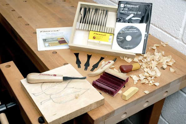 Flexcut carving tool set on workbench with wood held in vice.