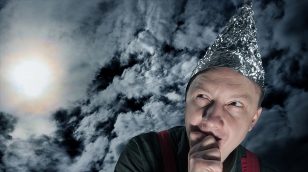 Scared-Suspecting-Man-Wearing-A-Foil-Hat-Against-Dark-Stormy-Sky-Shutterstock