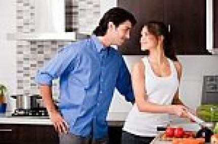 couple-staring-each-other-eyes-in-the-kitchen-10040385