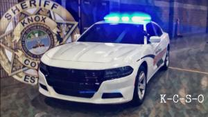 KCSO cruiser with lights on and badge overlay