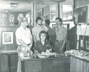 Three men standing around a woman at desk
