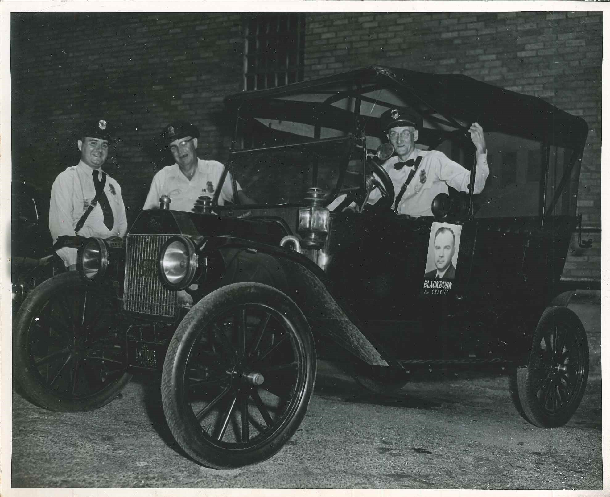 Black and white photo of three officers in and near old style motor vehicle