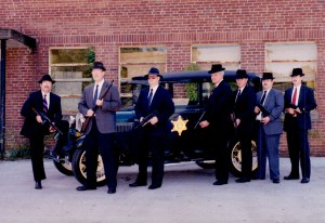 Officers in suits posing with guns and old 1940's vehicle