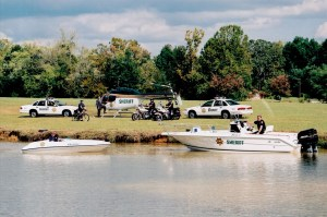 KCSO helicopter, boats, motorbikes, and cruisers parked on grass and in water