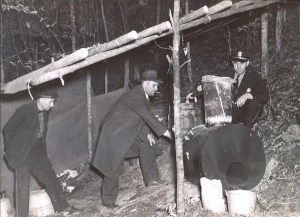 black and white image of officers investigating moonshine still