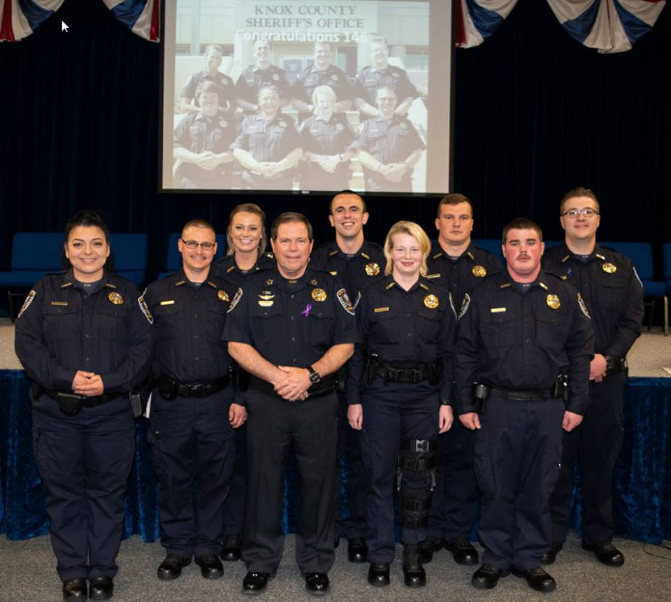 Sheriff posing with new COTA graduates