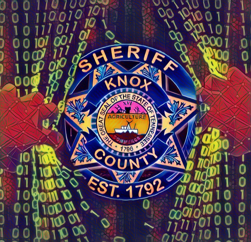 Digital KCSO badge behind curtain of 1s and 0s