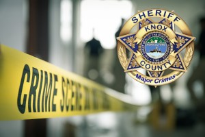 Blurred taped off crime scene with KCSO badge overlay