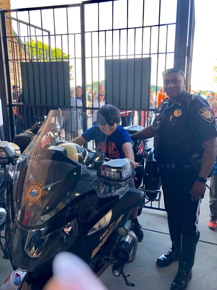 Officer smiling with boy on KCSO motorbike