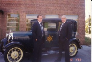 Officers wearing suits in 1992 standing next to 1940'2 model cruiser