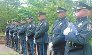 Honor Guard officers standing at attention in line with rifles and one folded american flag