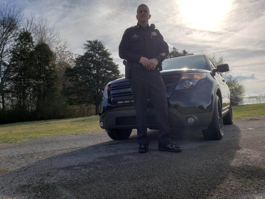 Lower view of Captain Smith standing in front of black SUV
