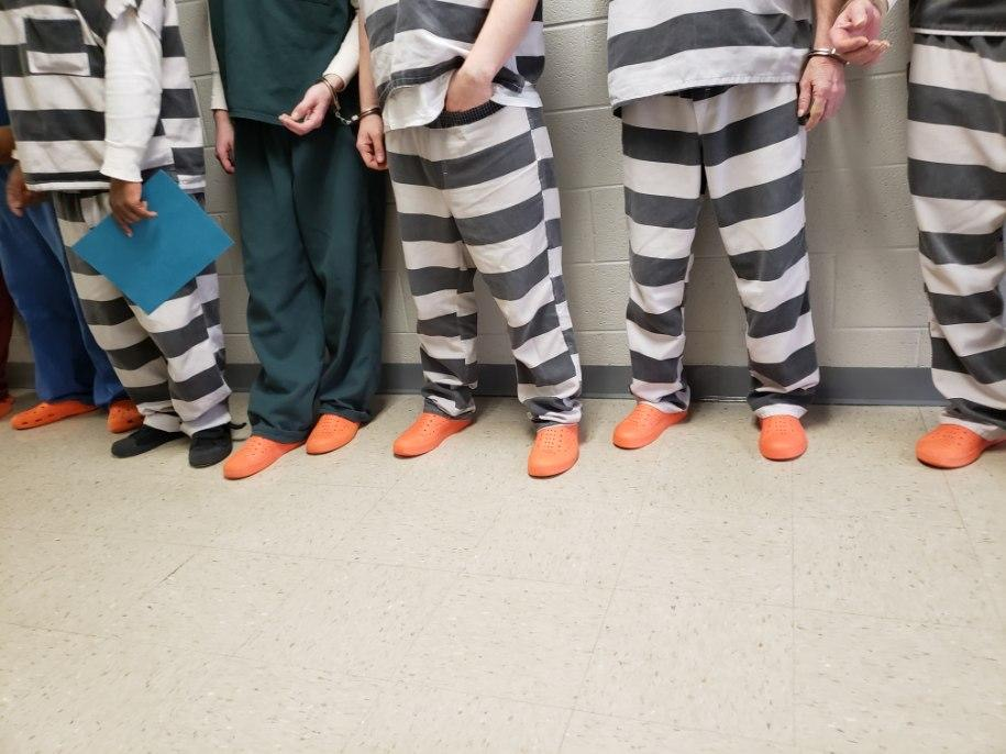 Image of inmate legs and feet standing in line for transport