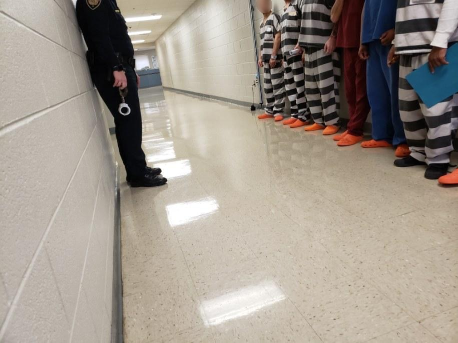 Officer speaking to inmates standing along wall
