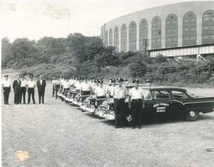 Older black and white image of Sheriff deputies next to older model cruisers