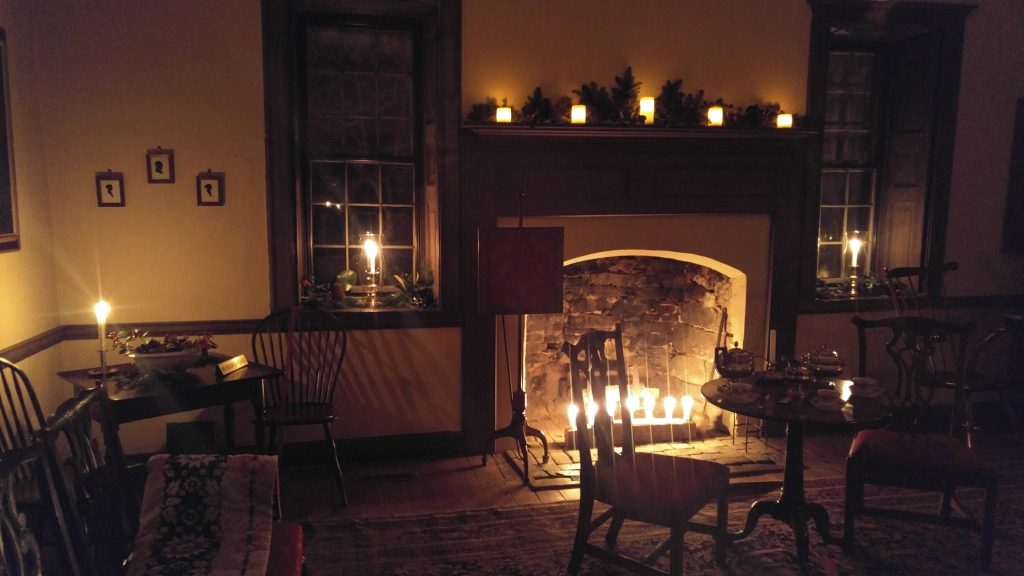Tables and chairs next to lit fireplace and candles