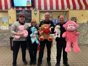 Officers holding stuffed animals and smiling