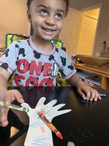 Child smiling with colored hand cutout