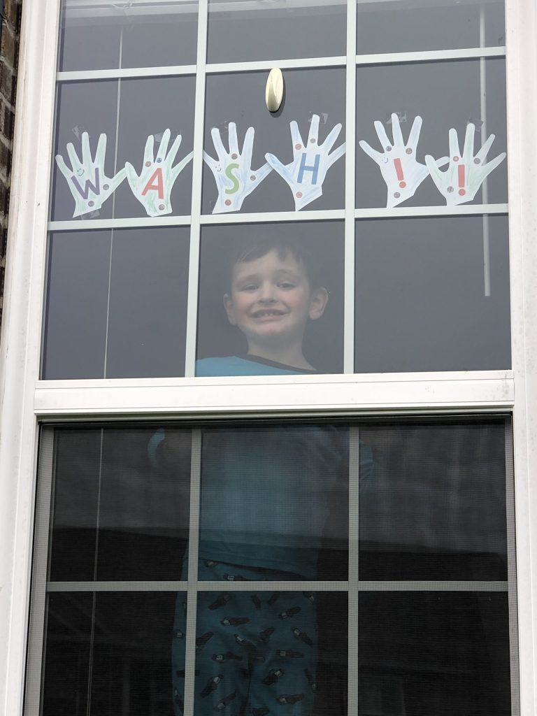 Child smiling through window with hand cutout