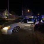Silver wrecked car with driver door open at night