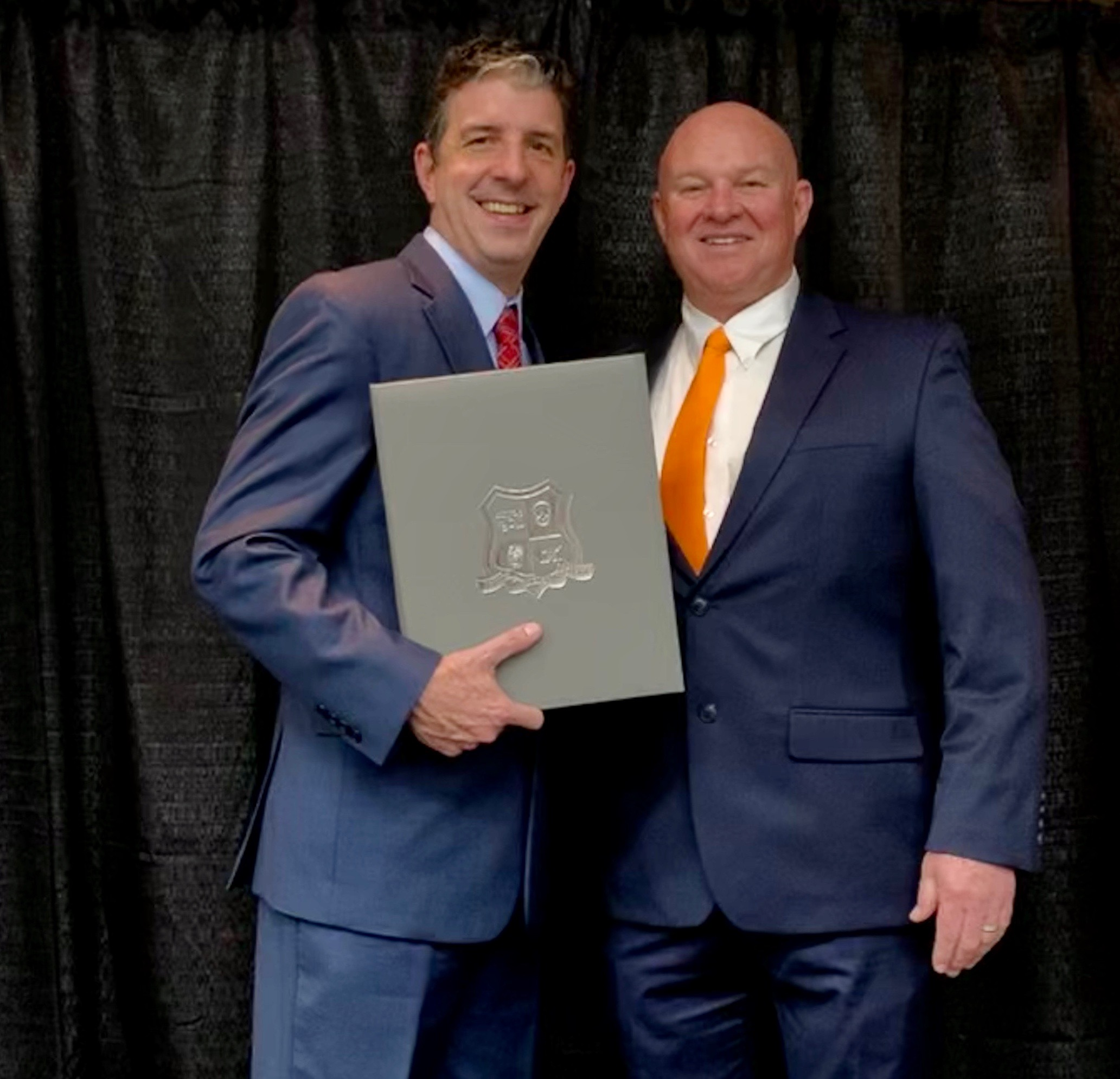 Mullinax in suit posing with anothe rman in suit holding award