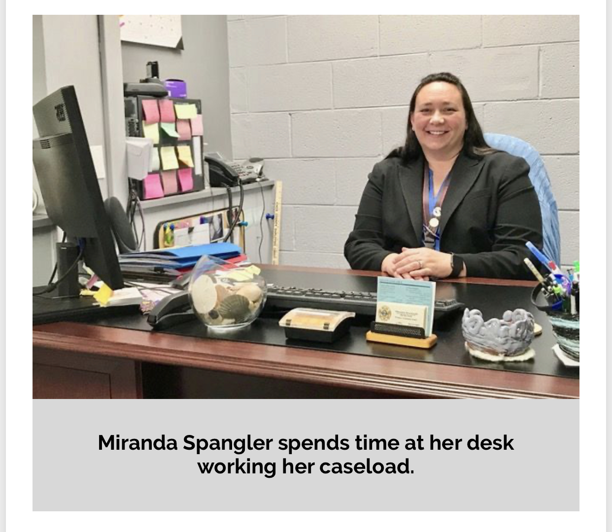 Detective Spangler smiling at desk
