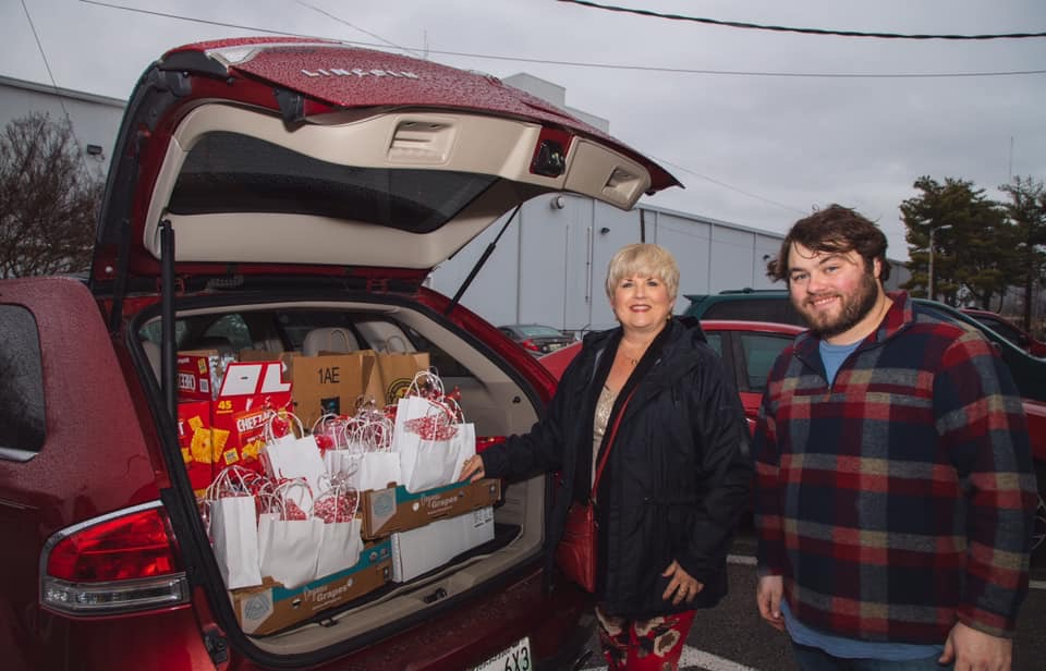 Man and woman smiling at back of car with trunk open and lots of gift bags within