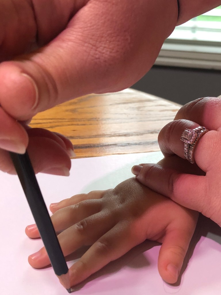 adult hands helping child trace hands