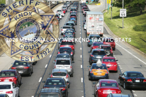 """2020 Weekend Memorial Day Stats with opaque KCSO badge and traffic in background"