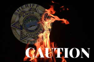 "Sheriff badge with flame overlay and ""Caution"""