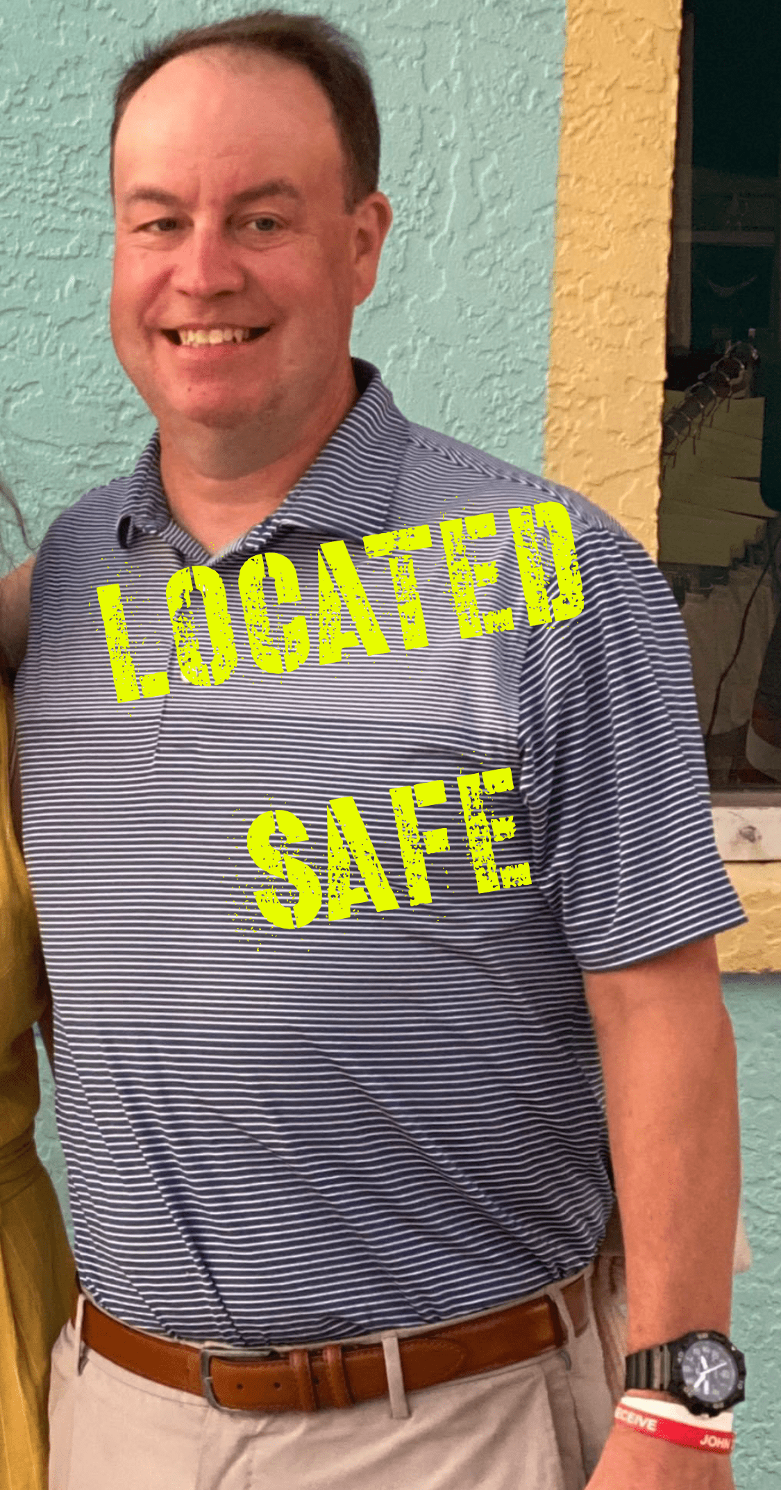 "Smiling man in striped shirt and ""Located Safe"" overlay"