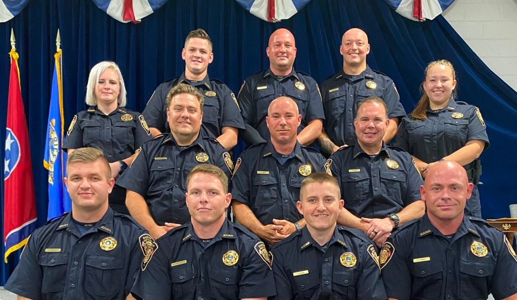 12 recent graduating officers posing for camera
