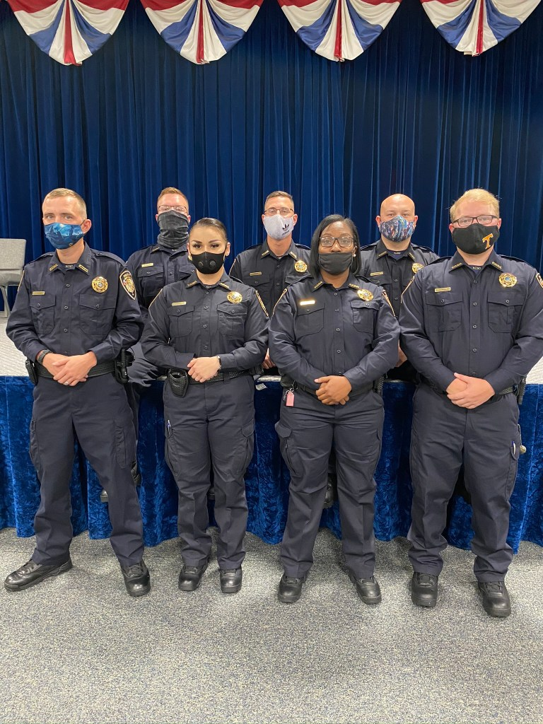 7 Graduating Officers posing for camera with masks on