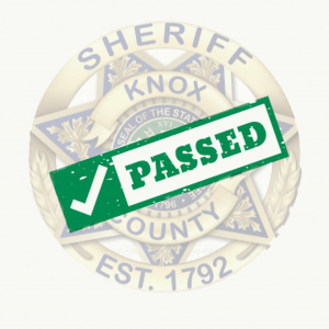 "KCSO badge with ""Passed"" stamp"