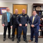 Corporal Thomas smiling with Sheriff, Chief Deputy, and Chief Purvis