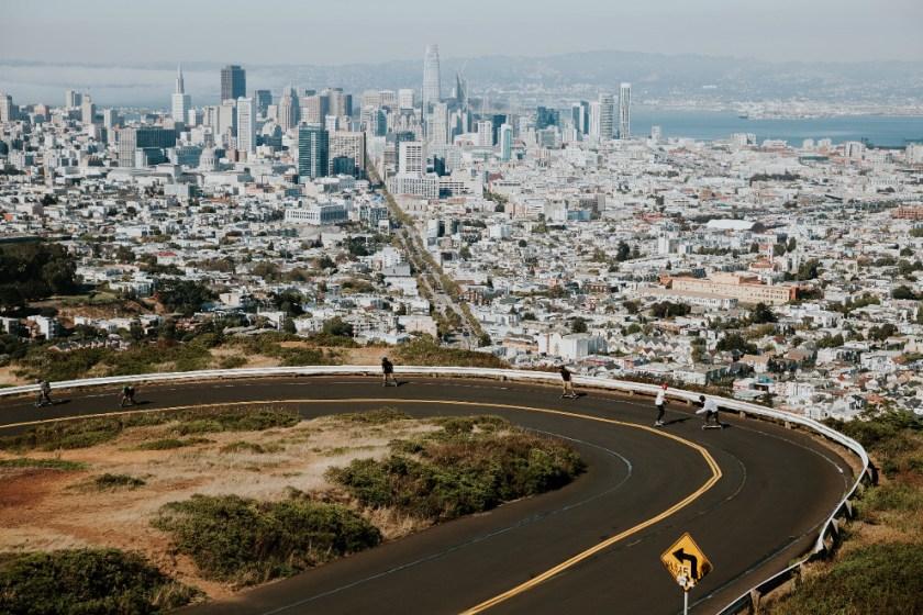 A few people skateboarding down Twin Peaks Blvd. in San Francisco on a sunny day.