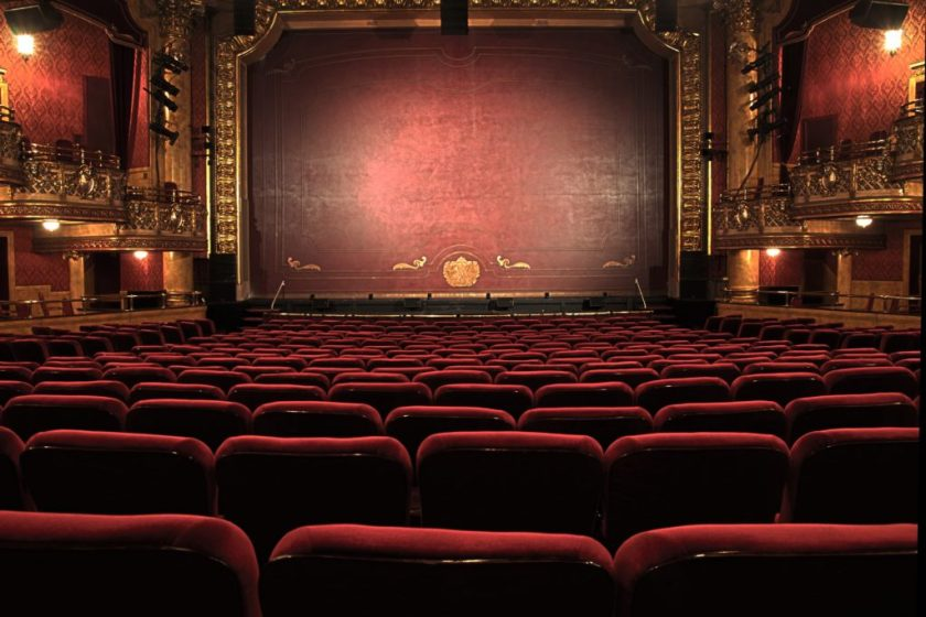 An empty old-fashioned theater, with gilded walls and a red velvet curtain.