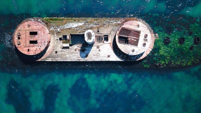 Bird's eye view of a sunken battleship in clear blue water.