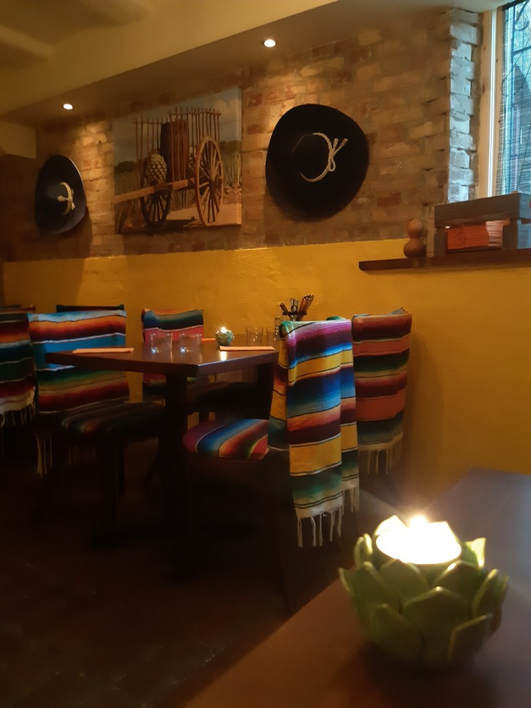 Interior shot of an empty Mexican restaurant with bright yellow walls, black sombreros hanging from the wall, and chairs upholstered in bright stripes.
