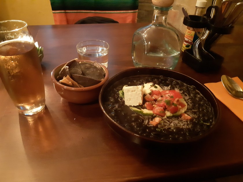 A bowl of black soup with diced tomatoes and avocado in a brown clay bowl, with a small bowl of nachos on the side.