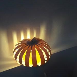 lampe à poser en lames de bois. feuilles de bois fines alternées clair et obscur; lumière jaunatre et transparence des veines du bois