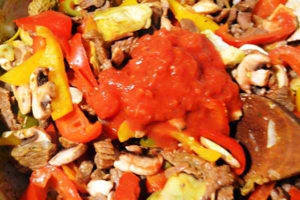 Rindergeschnetzeltes mit Zwiebel und Knoblauch , Paprika , Artischocken Pilzen Jalapenos und Tomaten anbraten