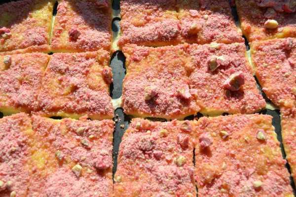 geschnittener Hefeteig ausgerollt mit rosa kandierten gehackten Mandeln