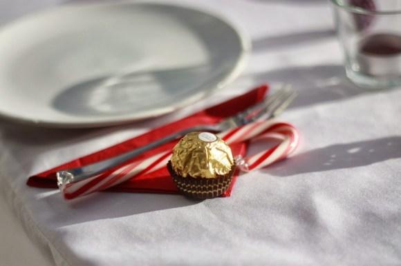 Variante in rot: Rote Serviette, goldenes Rocher und rot-weißer Candy-Stab