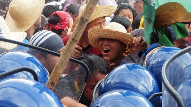 A straw hat-wearing activist shouting the command to comrades to not retreat from the helmeted police assault.