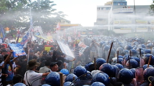 The police again advance behind water blasts as the protesters hold up their signs  in defiance.