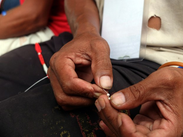 A Manobo farmer's thick fingers are deft enough to hold the tiny glass beads and thread them through fine strings.