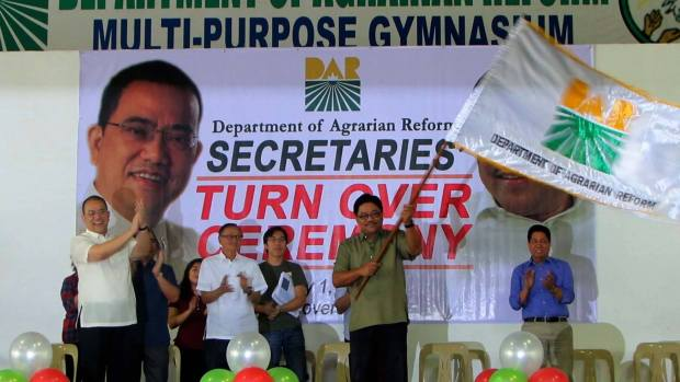 Rafael 'Ka Paeng' Mariano waves the Department of Agrarian Reform flag at yesterday's turn over ceremony. (Photo by Divine Miranda)