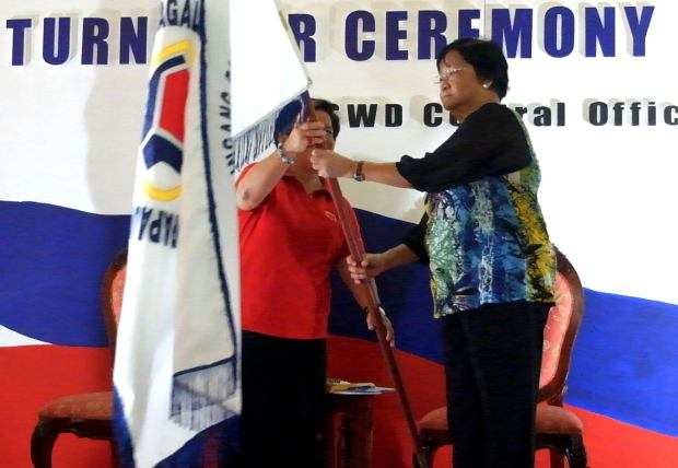 Secretary Taguiwalo receives the DSWD flag from her predecessor Corazon Soliman at last Friday's turn over ceremony.