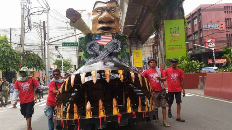 """Duterte effigy """"Dut-in-Boot"""" being rolled to Mendiola to be burned by participants of Lakbay Magsasaka. (Photo by Kathy Yamzon)"""